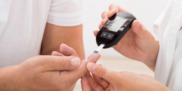 Doctor Using Glucometer On Patient's Finger
