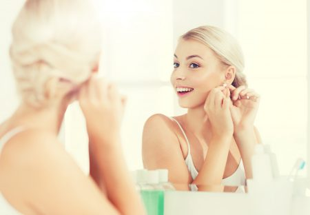 beauty, jewelry and people concept - smiling young woman trying on diamond earring and looking to mirror at home bathroom
