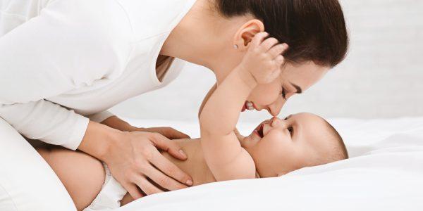 Mutter spielt mit Ihrem Kind im Schlafzimmer