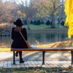 Frau sitzt im Herbst auf einer Bank
