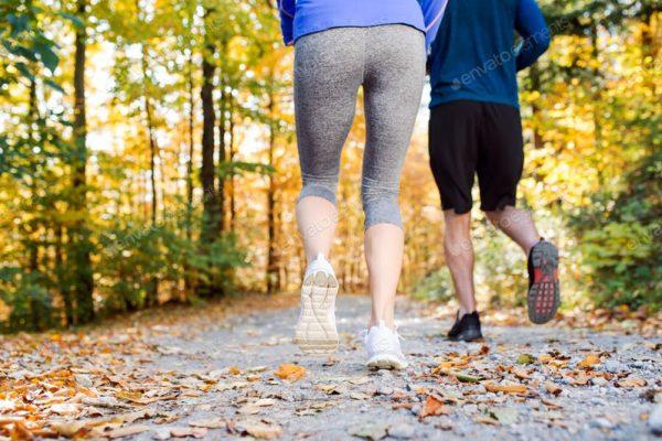 Älteres Ehepaar in SPortkleidung geht im Herbst Joggen