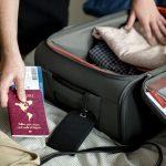 Mann bereitet sich auf einen Sommerurlaub vor und packt seine Koffer mitsamt seiner Reiseapotheke