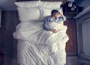 Mann im Bett wacht auf, weil er an Kopfschmerzen und Migräne leidet