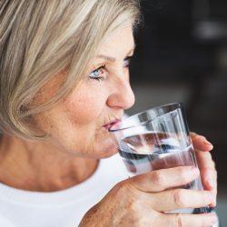 Alte Frau beugt Ihren Kopfschmerzen vor und trinkt viel Flüssilgkeit in FOrm von Wasser