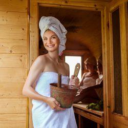 Frau in Sauna beugt ihre Kopfschmerzen vor