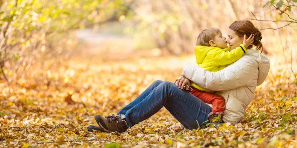 Herbst ist da. Frau mit kleinem Kind spielt im Laub während eines Spazierganges